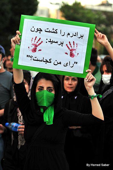 """Ung iransk kvinde demonstrerer efter valgsvindlen i Iran 2009. På banneret står der: De slog min bro ihjel, fordi han spurgte """"hvor er min stemme?"""" Foto Hamed Saber, fra Wikipedia."""