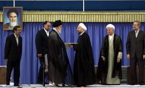 Fra Pr. Hassan Rouhanis indsættelse i august 2013. Ayatollah Khamenei, Irans øverste leder ses overrække Rouhani et eller andet. Øverst til venstre hænger et portræt af den islamiske revolutions leder, Ayatollah Khomeinei, som i 1979 smed Irans sidste Shah (konge) på porten. Shah Reza Pahlavi var indsat af amerikanerne efter et kup i 1953 på den demokratisk valgte premiereminister, Mohammed Mossadeq. Foto fra den iranske Præsidents hjemmeside.
